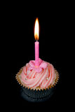 Cup cake and candle. Beautifully decorated pink cupcake and candle on black background Stock Images