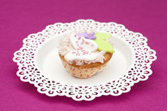 Cake Cup-Cake Fresh Baked. A freshly baked and decorated cup cake on a white plate with a pink background Royalty Free Stock Image