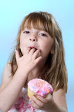 Cup Cake Fun. Adorable little girl eating cup cake with frosting on her lips stock photos