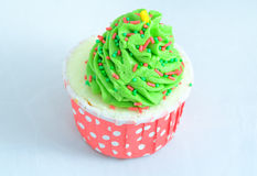 Cup cake with green icing and candies Stock Photos
