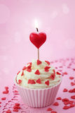 Cup cake with heart candle. On pink background royalty free stock images