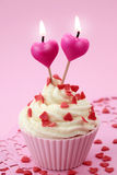 Cup cake with heart candles. On pink background stock photo