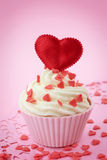Cup cake with heart shaped decoration. On pink background stock photo