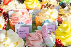 Cup cake heaven. Take your pick from multiple iced top cakes, topped candy and sweets. Chocolate and sugar topped cup cakes. Marsh Mallow, sugar coated candy Royalty Free Stock Photo