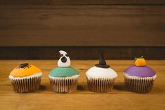 Cup cakes arranged on wooden table during Halloween. Colorful cup cakes arranged on wooden table during Halloween Royalty Free Stock Photography
