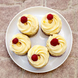 Cup-cakes close-up with raspberry on top. Delicious sweet buffet with cupcakes on the plate Stock Photography