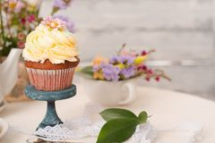 Cup cakes with cream cheese topping on beautiful wooden cake sta. Nd with flowers and wooden background behind it, spring mood still life photo for holiday Stock Photos
