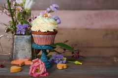 Cup cakes with cream cheese topping on beautiful wooden cake sta. Nd with flowers and wooden background behind it, spring mood still life photo for holiday Royalty Free Stock Images