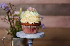 Cup cakes with cream cheese topping on beautiful wooden cake sta. Nd with flowers and wooden background behind it, spring mood still life photo for holiday Royalty Free Stock Photography