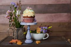 Cup cakes with cream cheese topping on beautiful wooden cake sta. Nd with flowers and wooden background behind it, spring mood still life photo for holiday Stock Image