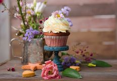 Cup cakes with cream cheese topping on beautiful wooden cake sta. Nd with flowers and wooden background behind it, spring mood still life photo for holiday Royalty Free Stock Photo