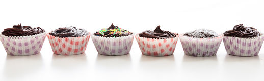 Cup cakes in a row on a white background. Cup cakes on a white background Royalty Free Stock Image
