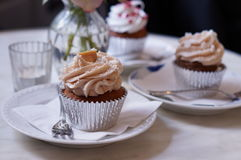 Cup cakes on table with table with garnishes Royalty Free Stock Photo