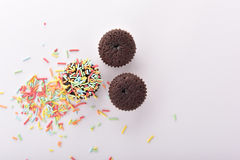 Three cupcakes on white background with sprinkles. Three cupcakes on white background. One of them has colourful scattered sprinkles on top Royalty Free Stock Image