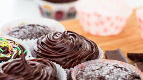 Cup cakes on a wooden surface. Cup chocklate cakes on a wooden surface Royalty Free Stock Image