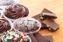 Cup cakes on a wooden surface. Cup chocklate cakes on a wooden surface Royalty Free Stock Photo