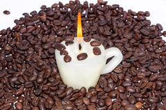 Cup candle with warm flame in roasted coffee beans Stock Photography