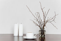 Cup, candles and branches in bottle on a wooden table. Romantic grey and white still life royalty free stock photos