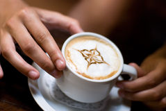 A cup of cappuccino. In hand Stock Photo