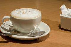 Cup of cappuccino. White cup of cappuccino with sugar royalty free stock photos