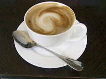 Cup of cappuccino. Cappuccino cup with teaspoon, photographed in Italian restaurant in Udine Royalty Free Stock Image