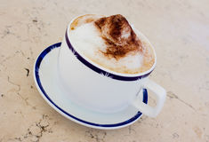 Cup of cappuccino. With cacao and sugar on a marble table Royalty Free Stock Image
