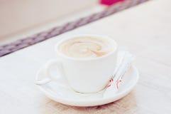 Cup Cappuccino auf der Tabelle Lizenzfreie Stockfotos