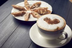 Cup of cappuccino with beautiful heart latte art on wooden table Near plate with dessert. Flat lay style. Cup of cappuccino with beautiful latte art on wooden royalty free stock photography