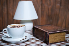 Cup of cappuccino at the book closeup Royalty Free Stock Photo