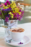Cup of cappuccino and bouquet of flower; selective focus; toned. Cup of cappuccino and bouquet of wildflowers in summer terrace of cafe Royalty Free Stock Photography