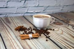 A cup of cappuccino, a bunch of cinnamon, coffee beans and star anise lie on a wooden table. Close-up stock photography