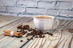 A cup of cappuccino, a bunch of cinnamon, coffee beans and star anise lie on a wooden table. Close-up stock images