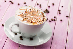 Cup of cappuccino and chocolate topping with coffee beans on pink wooden background, hot drink produact photography  on wh Stock Photo