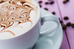 Cup of cappuccino and chocolate topping with coffee beans on pink wooden background, hot drink produact photography  on wh Royalty Free Stock Photo