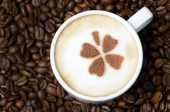 Cup of cappuccino with cinnamon pattern on a background of coffe Stock Photo