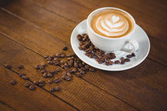 Cup of cappuccino with coffee art and coffee beans. On wooden table Royalty Free Stock Image
