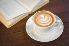 Cup of cappuccino with coffee art next to opened book stock photo