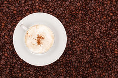 A cup of cappuccino on coffee beans background Royalty Free Stock Photos