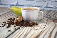 A cup of cappuccino, coffee beans, a bunch of cinnamon and a pear are lying on a wooden table against a white brick wall. Close-up. A cup of cappuccino, coffee royalty free stock image