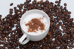 Cup of cappuccino coffee with beans. On wood table Stock Photo