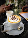 Cup of cappuccino coffee during busy working hours Stock Images