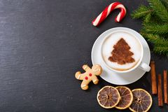 Cup of cappuccino coffee with christmas tree drawing and ginger. Christmas drink. Cup of cappuccino coffee with christmas tree drawing and gingerbread cookie royalty free stock photo