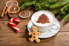Cup of cappuccino coffee with christmas tree drawing and ginger. Christmas drink. Cup of cappuccino coffee with christmas tree drawing and gingerbread cookie stock image