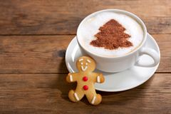 Cup of cappuccino coffee with christmas tree drawing and gingerbread cookie. Christmas drink. Cup of cappuccino coffee with christmas tree drawing and royalty free stock photo