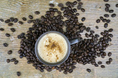 Cup of cappuccino coffee with coffee beans Royalty Free Stock Image