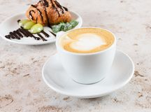 Cup of cappuccino coffee and the croissant Royalty Free Stock Image