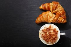 Cup of cappuccino coffee and croissants on dark table stock images