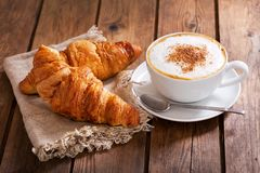Cup of cappuccino coffee with croissants Royalty Free Stock Photo