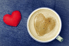Cup of cappuccino coffee with foam in the form of heart on blue Royalty Free Stock Images