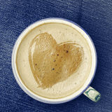 Cup of cappuccino coffee with foam in the form of heart on blue Royalty Free Stock Photo